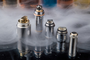 Electronic cigarette steel coils in a row with e-juice bottles in the background with misty smoke