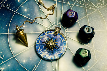 pendulum, astrology dice, zodiac ring with sun over a horoscope