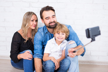 young parents and little son taking selfie photo