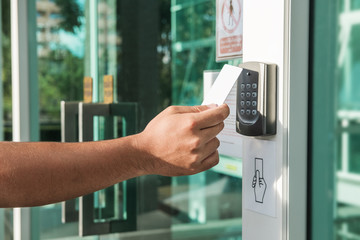 Hand using security key card scanning to open the door to entering private building. Home and building security system Wall mural