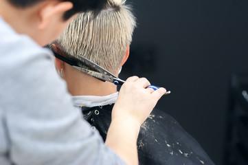 Women's haircut. Hairdresser, beauty salon. Professional hairdresser making stylish haircut. Hairdresser cutting woman bangs hair Process of hair cutting with use scissors