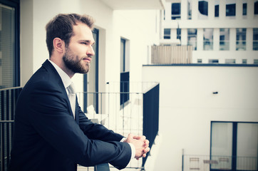 Handsome businessman enjoying view of the city from a balcony