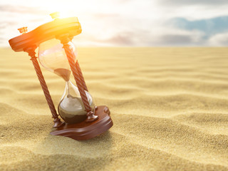 Hourglass clock on sand of desert background.