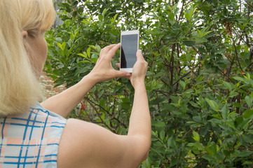 Blonde woman uses a smartphone to take a selfie in the Park in the summer