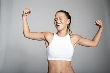 Blonde sportliche junge Frau zeigt ihre bizeps
