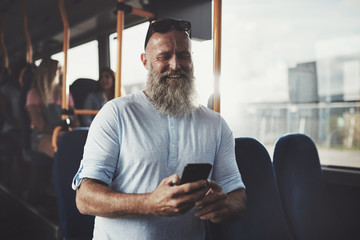 Mature man with a beard using his cellphone on the bus