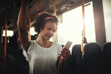 Smiling young African woman listening to music on a bus