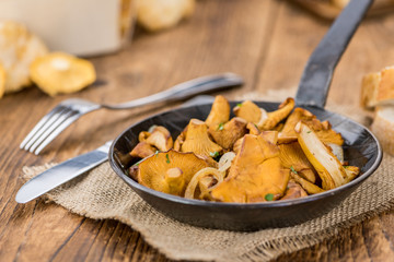 Fresh made Fried Chanterelles on a rustic background