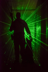 Police officer and dog silhouetted with green laser lights