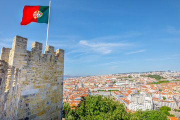 Lisbon aerial cityscape from Sao Jorge Castle on highest hill in Alfama. Waving portuguese flag on top of Lisbon Castle a popular tourist attraction. Panoramic view skyline of downtown on Tagus River.