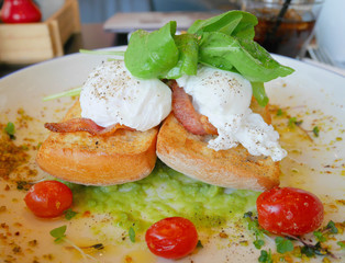 Eggs Benedict on toast with bacon, rocket salad, avocado sauce and tomato