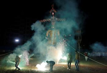 People light fireworks as an effigy of demon King Ravana is burnt during Vijaya Dashmi, or Dussehra festival celebrations, in Ahmedabad