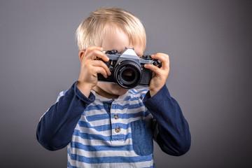 Junge mit analoger Kamera