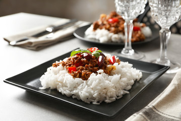 Chili con carne served with rice on dinner table