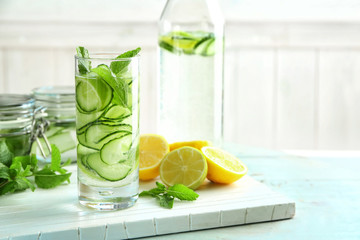 Glass of fresh cucumber water with lemon and mint on table