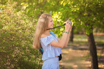 Beautiful young tourist taking photo outdoors