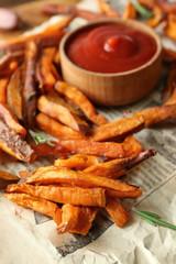 Deep fried sweet potato sticks with sauce on paper, closeup