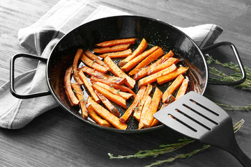 Frying pan with sweet potato fries on table