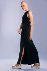 Beautiful bald woman in black dress on color background