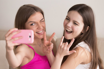 Two girlfriends taking selfie with smartphone, making funny faces, showing peace and rock on signs. Smiling girls make memories with photos together. Best friends take pictures for social media site.