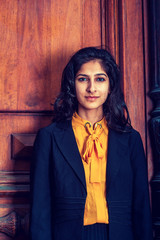 Modern East Indian American Woman with long curly hair  in New York. wearing black blazer, orange under shirt, standing by vintage style office doorway, looking at you..