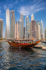Dubai Marina with boats against skyscrapers in Dubai, United Arab Emirates
