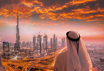 Arabian man watching cityscape of Dubai with modern futuristic architecture in United Arab Emirates.
