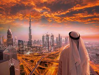 Arabian man watching cityscape of Dubai with modern futuristic architecture in United Arab Emirates.
