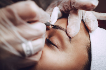 Closeup of a beautician hands applying japanese method of drawing on eyebrows to model.