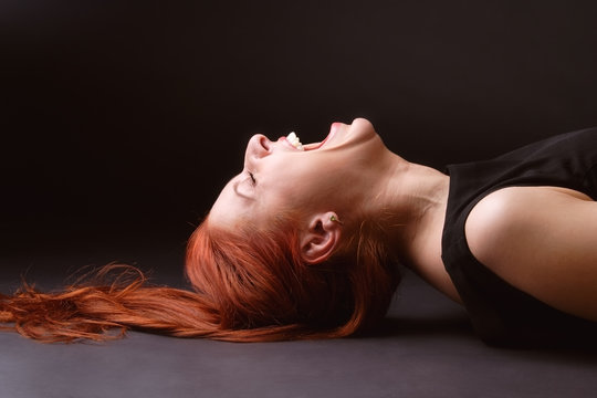 Red-haired woman lying ob the floor and hysterically laughing