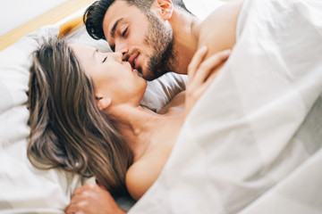 Young couple in love kissing in a bed under white blanket