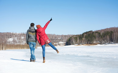 Couple walking on a frozen lake on a winter day