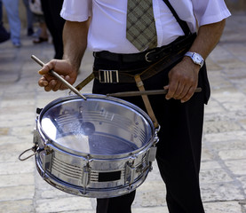 musician plays a drum on the street during a religious event