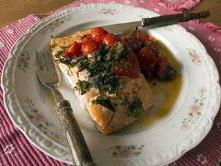Gebratener Lachs mit Tomaten auf einem Teller