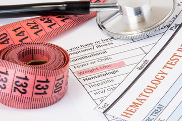 Photo idea of weight loss as symptom or sign of cancer endocrine diseases. Highlighted  during doctor consultations title weight loss symptom on patient history next to stethoscope and measuring tape