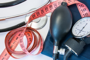 Weight gain or loss and high or low blood pressure concept. Measuring tape, stethoscope and sphygmomanometer. Effect of obesity, increased body weight or slimming on indicators of human blood pressure