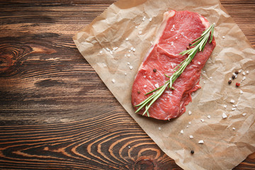 Fresh raw meat with spice on parchment paper