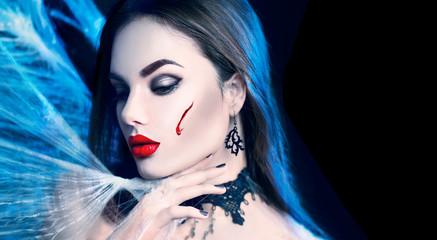 Halloween. Beauty sexy vampire woman posing in darkness, wearing spider web