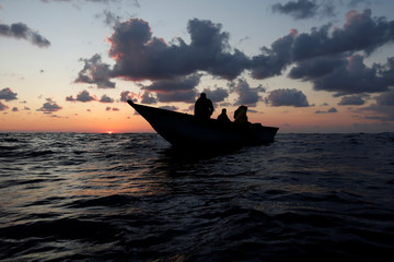 Libyan migrants on a wooden boat await rescue by the migrant search and rescue vessel MV Seefuchs of the German NGO Sea-Eye in the search and rescue zone some fifty nautical miles north of the Tunisian-Libyan land border