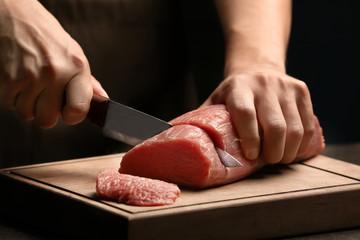 Chef cutting fresh raw meat on wooden board