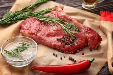 Fresh raw meat with rosemary on paper, close up