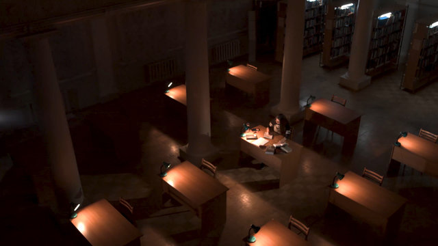 Top view of student hand writing a book with laptop at library. Girl sitting in empty library at night top view