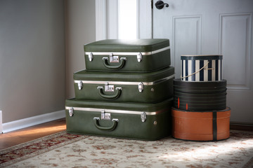 Set of vintage luggage and hatboxes waiting by the front door.