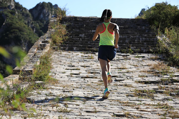 young fitness woman trail runner running on the great wall top of mountain