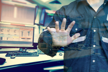 Double exposure of Engineer or Technician man  while using hand control monitor of computers room  for oil and gas industrial business concept