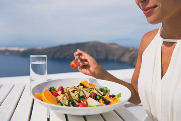 Wall Mural - Restaurant woman eating salad luxury europe travel Santorini vacation. Healthy lifestyle people relaxing on Greece holidays.
