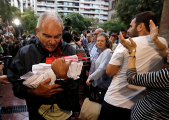 A  man holds ballots at a polling station for the banned independence referendum in Barcelona