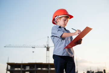 kid builder wearing orange helmet takes notes on building site background