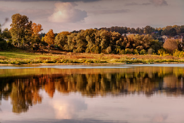 Beautiful river bank, autumn landscape with dramatic sky at sunset with reflection in water