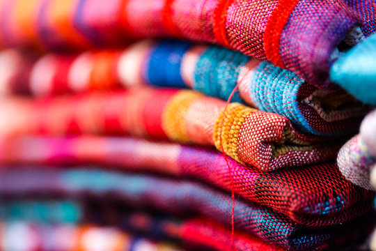 Colorful, vibrant red, blue, purple scarfs for sale on traditional medina souk